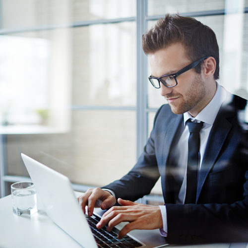 Businessman sitting at a laptop filling out a request a quote form online